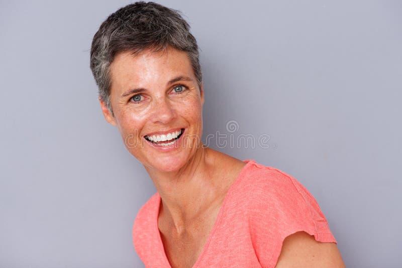 Feche acima da mulher atrativa da Idade Média que ri pelo fundo cinzento imagem de stock royalty free