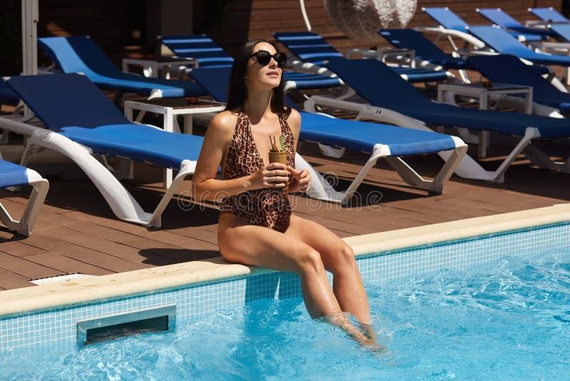 Feche acima da mulher bronzeada magro que senta-se na borda da piscina com cocktail à disposição, vestiu o terno nadador com cópi foto de stock