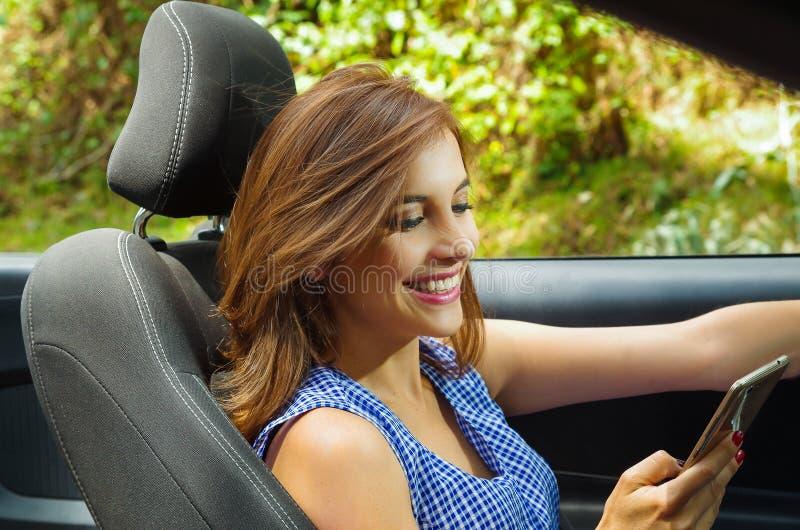 Feche acima da mulher caucasiano bonita que usa seu telefone celular dentro do carro preto, quando conduzindo no for borrada fotografia de stock royalty free