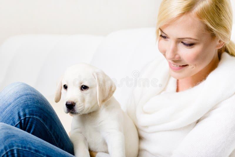 Feche acima da mulher com o filhote de cachorro em seus joelhos fotografia de stock