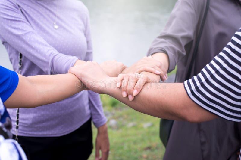 Feche acima da mulher das mãos que põem com pilha ou da mão que toca e que mostra nos trabalhos de equipe bem sucedidos junto ext imagem de stock