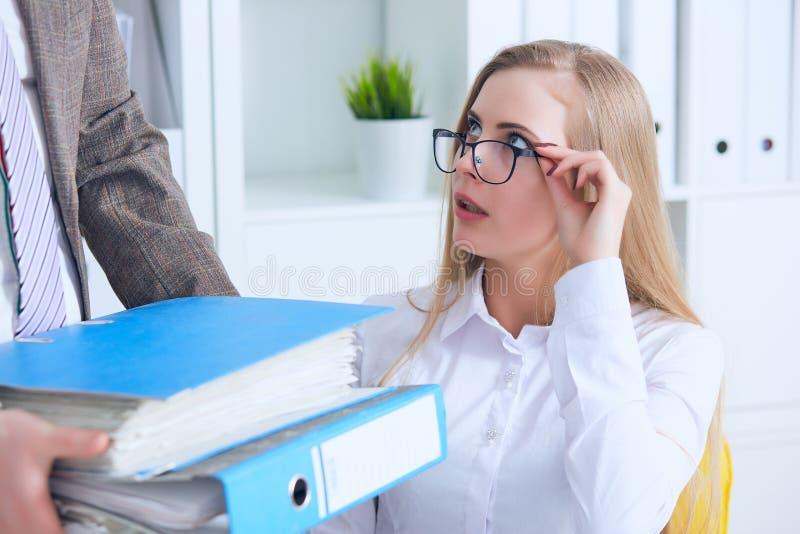 Feche acima da mulher de negócio da virada que toma dobradores com papéis da mão masculina do ` s do colega no escritório Negócio fotografia de stock
