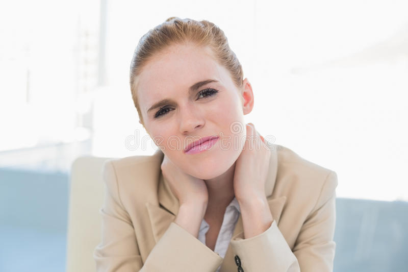Feche acima da mulher de negócios nova com dor de pescoço imagem de stock royalty free