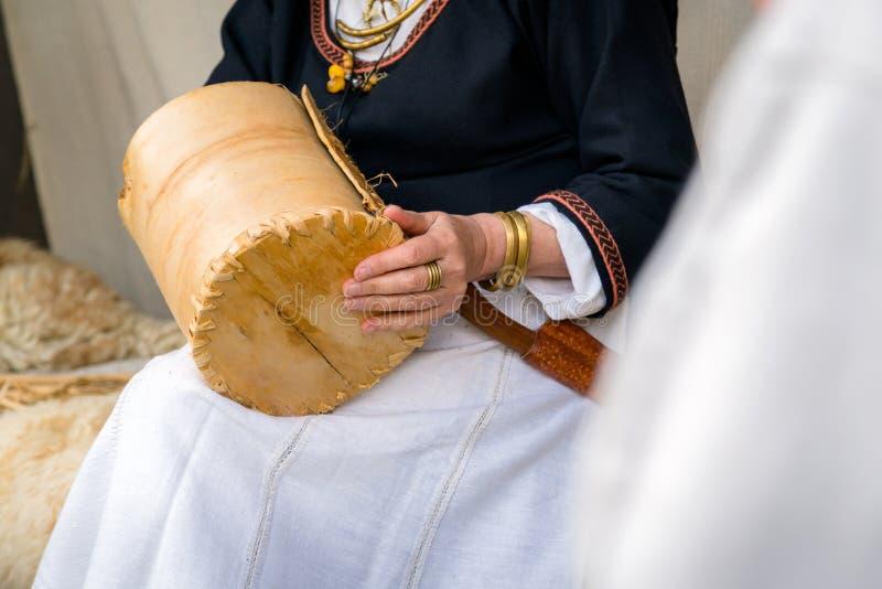Feche acima da mulher do artesão que veste a roupa rural que faz o vime imagem de stock
