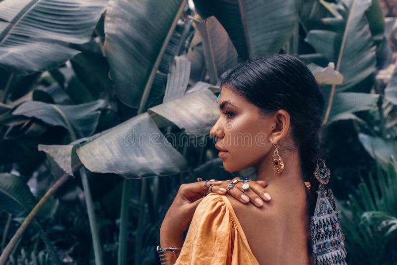 Feche acima da mulher elegante nova bonita com compõem e os acessórios à moda do boho que levantam no fundo tropical natural fotos de stock