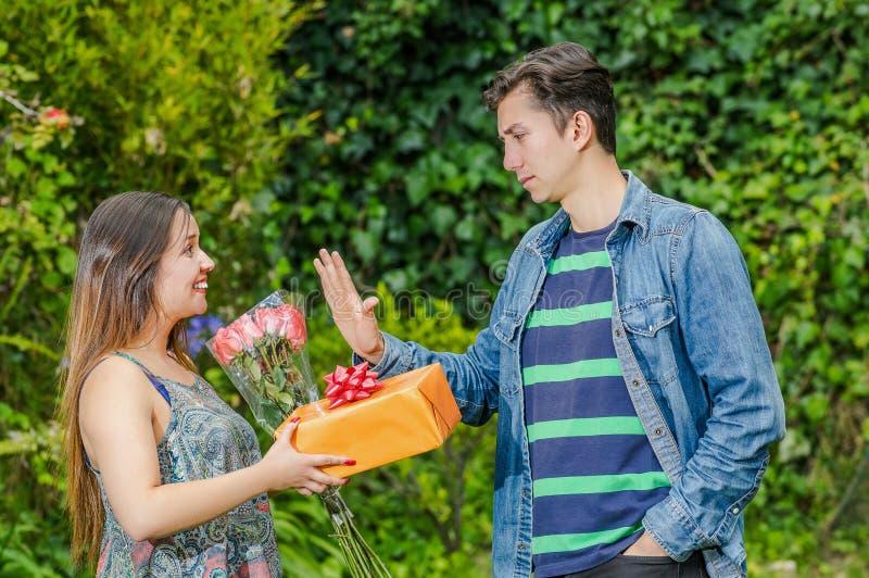 Feche acima da mulher feliz que mantêm um presente e as flores que olham seu esmagamento e do menino que estica seu braço que ign fotografia de stock royalty free