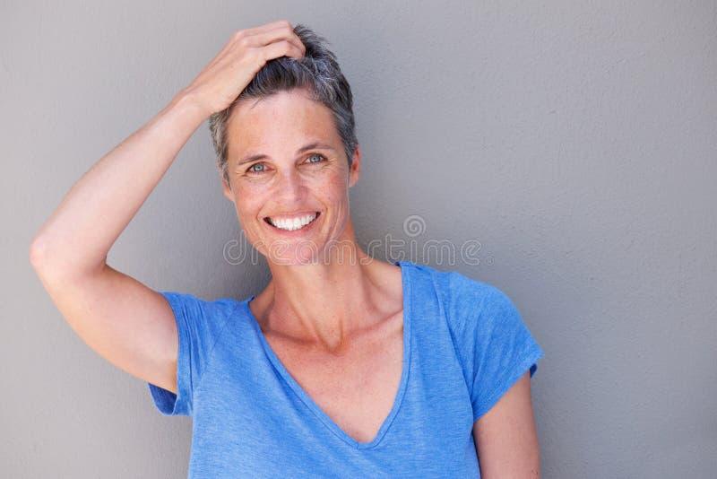 Feche acima da mulher feliz que ri com mão no cabelo imagens de stock royalty free