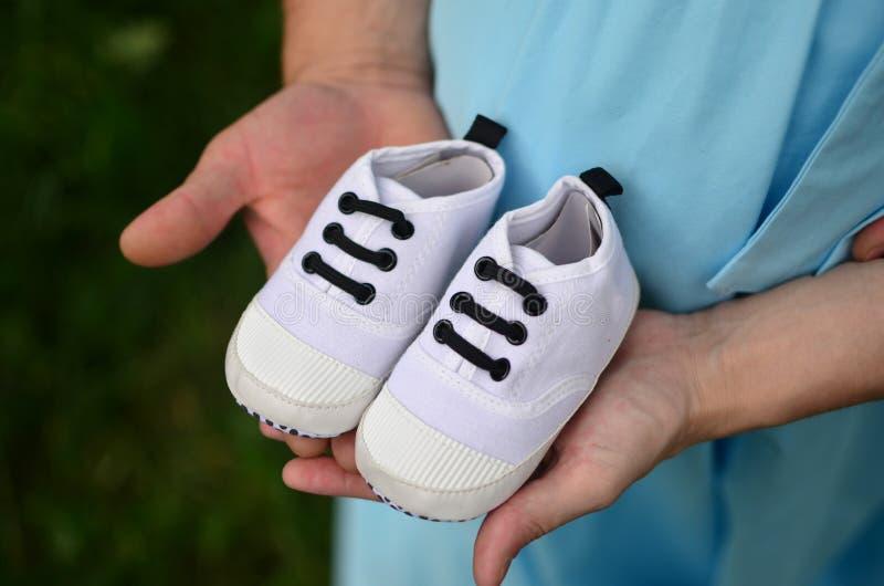 Feche acima da mulher gravida e dos homens guardando sapatas minúsculas na barriga imagem de stock royalty free