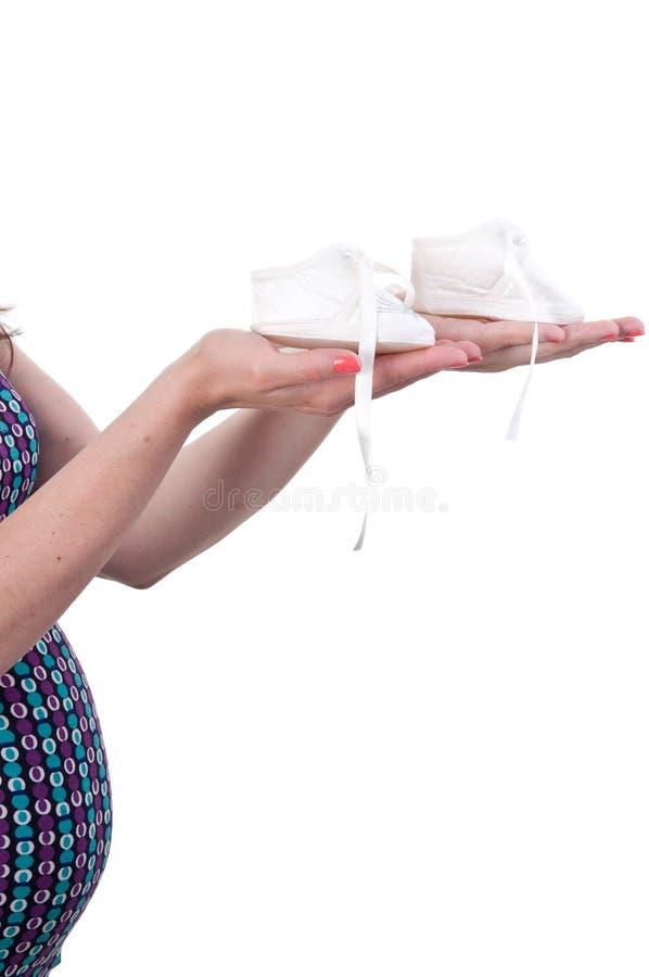 Feche acima da mulher gravida que guarda pares das sapatas brancas para o bebê, co imagem de stock