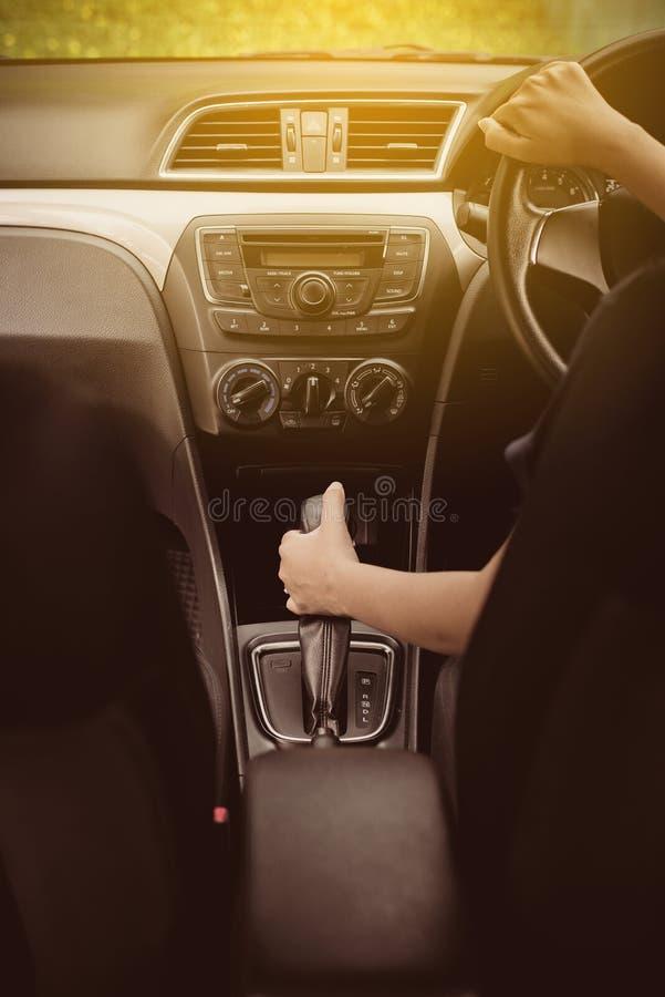 Feche acima da mulher da mão que guarda o volante e no deslocamento de engrenagem automático, conduzindo um carro fotografia de stock