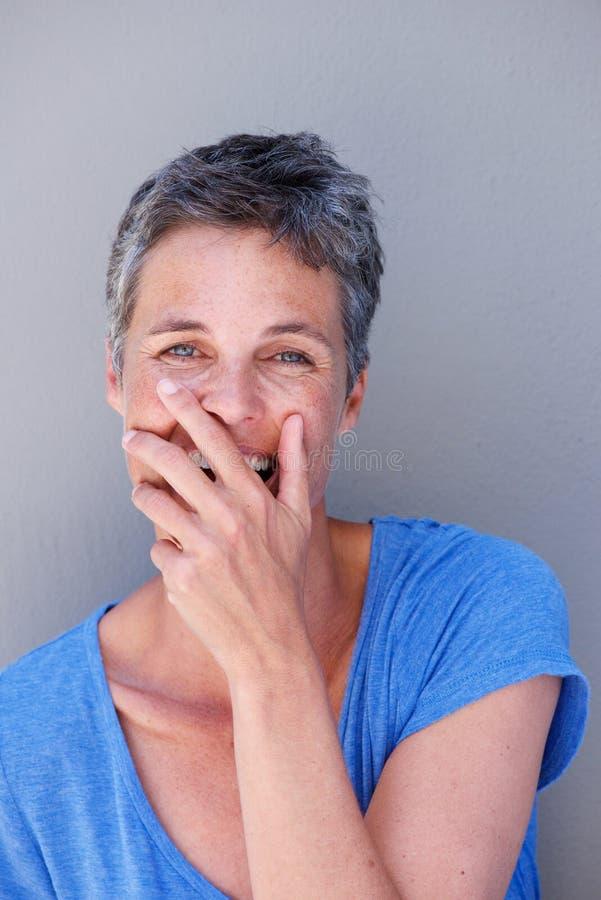 Feche acima da mulher mais idosa feliz que ri com a boca da coberta da mão fotografia de stock