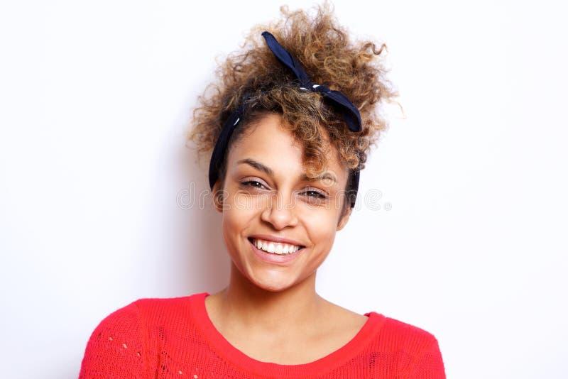 Feche acima da mulher negra nova bonita com bandana do cabelo que sorri contra a parede branca imagens de stock
