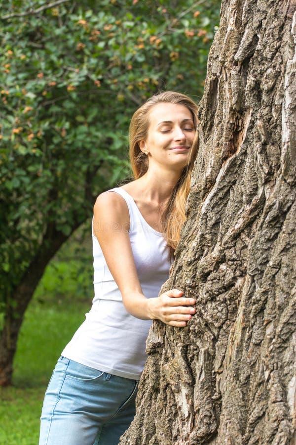 Feche acima da mulher nova pensativa do Natureza-amante que abraça uma árvore enorme foto de stock