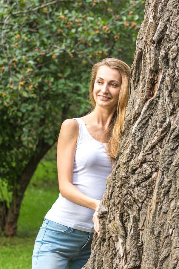 Feche acima da mulher nova pensativa do Natureza-amante que abraça uma árvore enorme fotos de stock