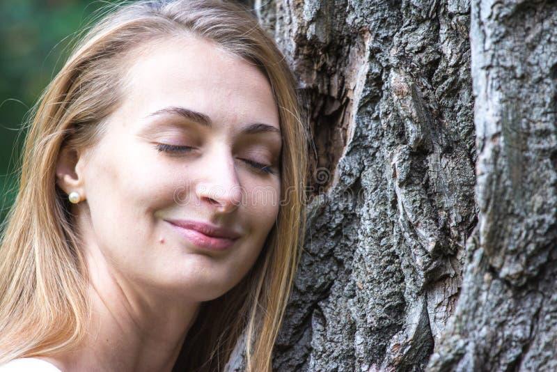 Feche acima da mulher nova pensativa do Natureza-amante que abraça uma árvore enorme fotografia de stock