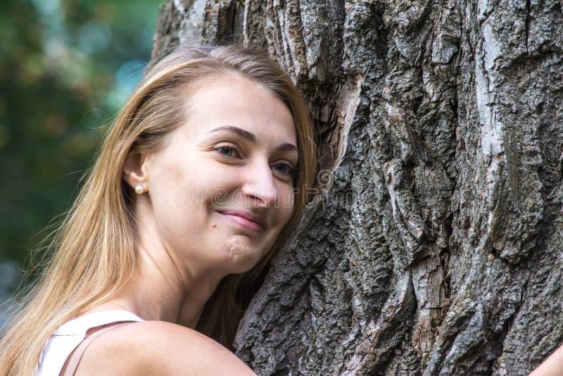 Feche acima da mulher nova pensativa do Natureza-amante que abraça uma árvore enorme fotografia de stock royalty free