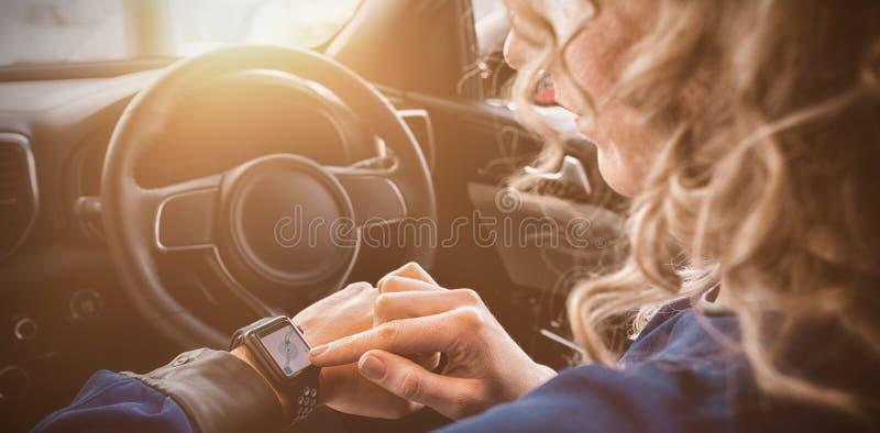 Feche acima da mulher que usa o relógio esperto no carro foto de stock