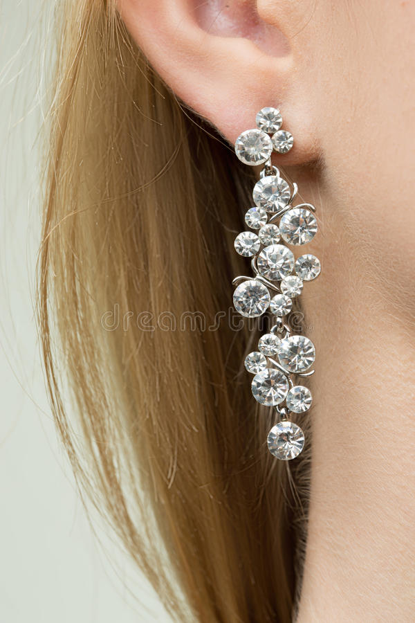 Feche acima da mulher que veste brincos brilhantes do diamante foto de stock