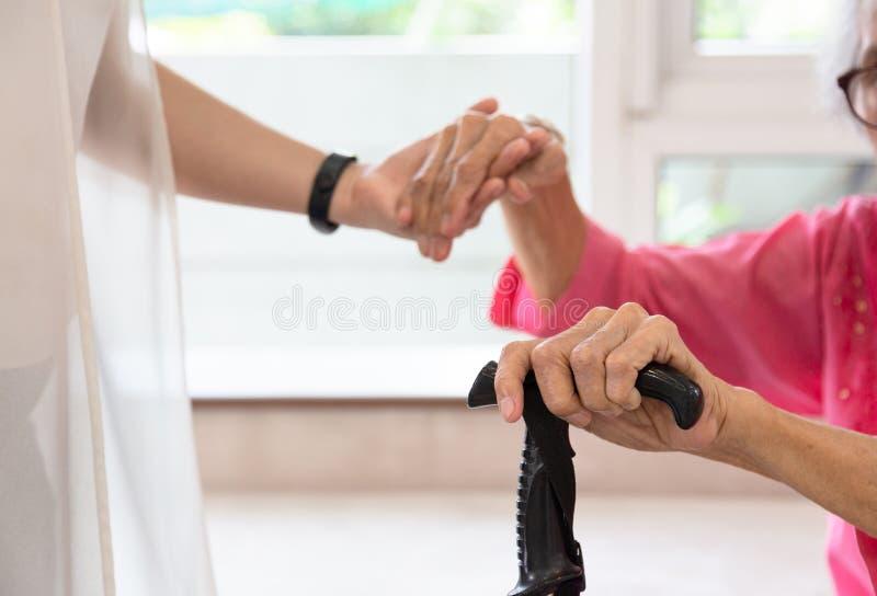 Feche acima da mulher superior e da jovem mulher que guardam a mão, pessoa, AG fotografia de stock