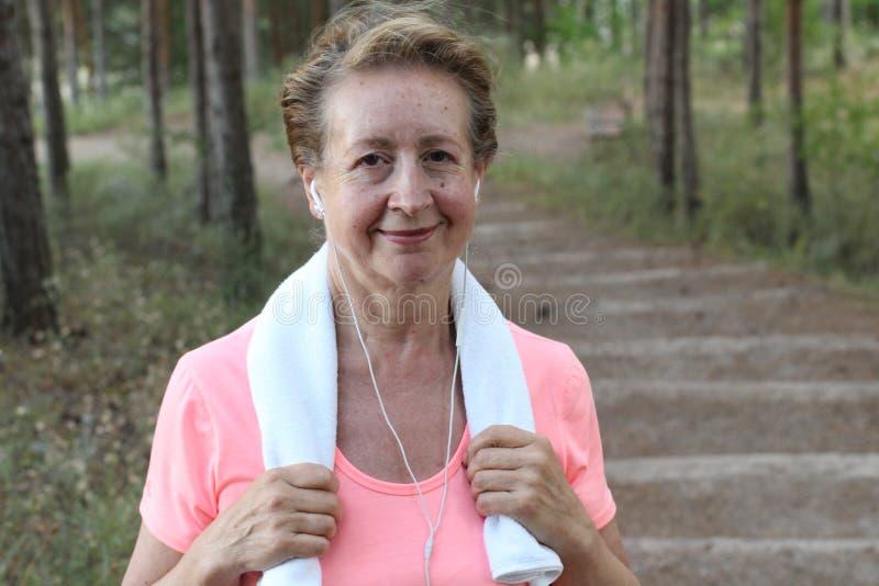 Feche acima da mulher superior que corre no parque que escuta a música que guarda uma toalha imagem de stock