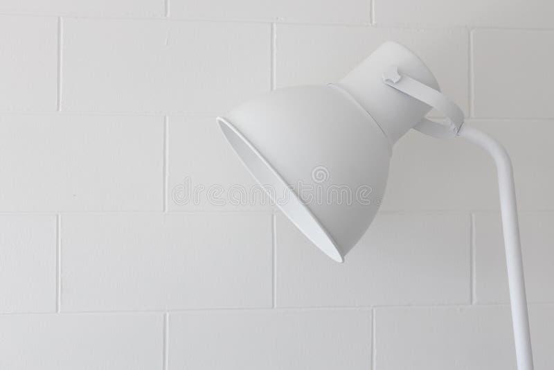 Feche acima da ?nica l?mpada branca moderna simples ajust?vel no fundo da textura da parede de tijolo do bloco fotografia de stock