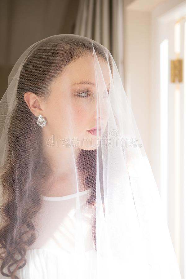 Feche acima da noiva bonita que está pela janela imagem de stock