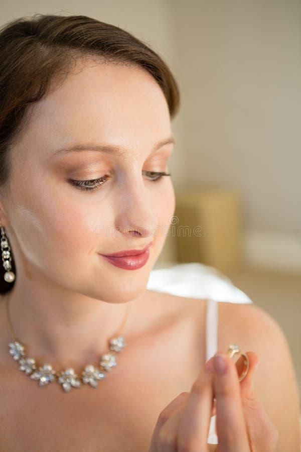 Feche acima da noiva bonita que olha a aliança de casamento em casa fotos de stock royalty free