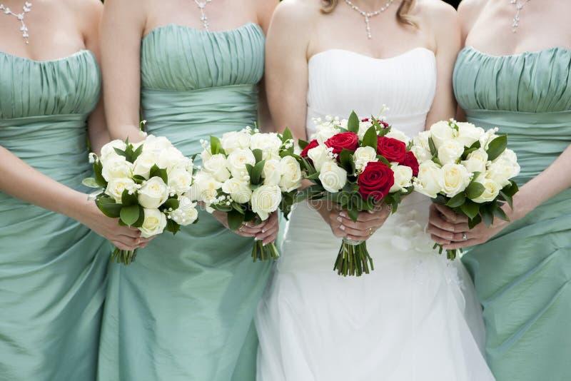 Feche acima da noiva e das damas de honra que guardam flores fotografia de stock royalty free
