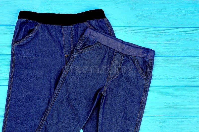 Feche acima da obscuridade - calças de brim azuis do estiramento para a criança imagens de stock