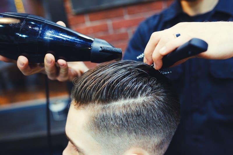 Feche acima da opinião lateral o homem que obtém o corte de cabelo na moda pelo cabeleireiro com o secador de cabelo no barbeiro imagem de stock royalty free