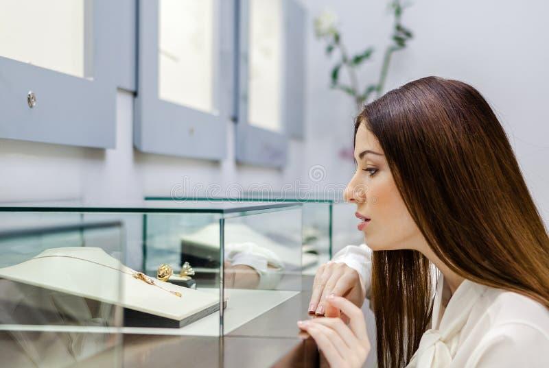 Feche acima da opinião a menina que olha a joia no caso de vidro fotografia de stock royalty free