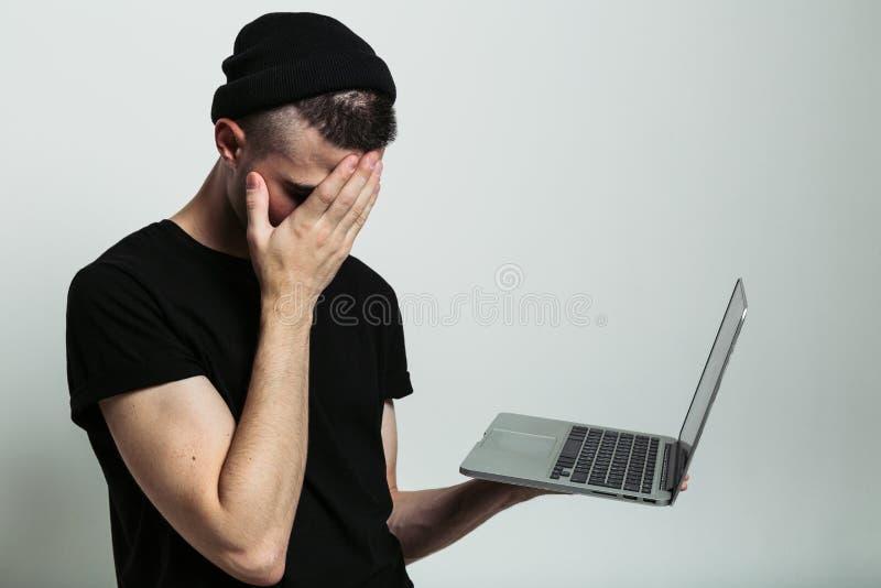 Feche acima da opinião o homem com portátil e facepalm imagens de stock