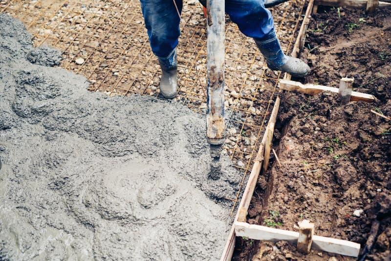 Feche acima da opinião o trabalhador que segura um cimento maciço ou uma bomba concreta no canteiro de obras foto de stock