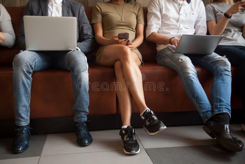 Feche acima da opinião os povos diversos que sentam-se usando dispositivos eletrónicos imagem de stock