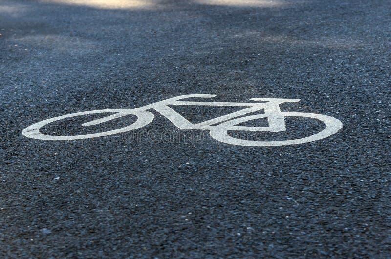 Feche acima da opinião um ciclista pintado no branco em uma trilha de ciclo do asfalto Sinal de tráfego indicar um trajeto da bic fotografia de stock royalty free