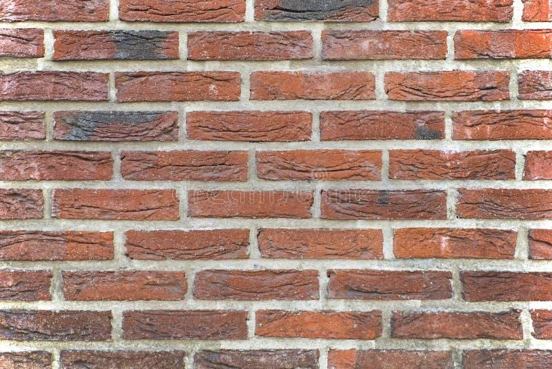 Feche acima da parede de tijolo da cor vermelha Tijolos velhos com traços do fogo Fundo perfeito foto de stock
