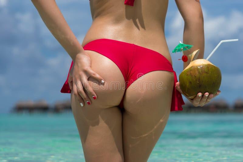 Feche acima da parte traseira da menina no biquini contra a praia e o coco do oceano fotografia de stock
