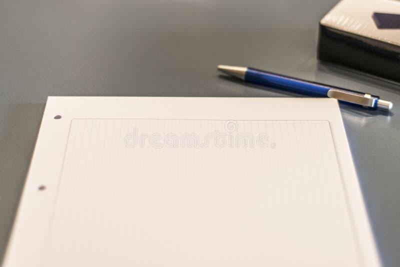 Feche acima da pena escura da tabela de conferência, da folha de papel e do fundo obscuro imagem de stock