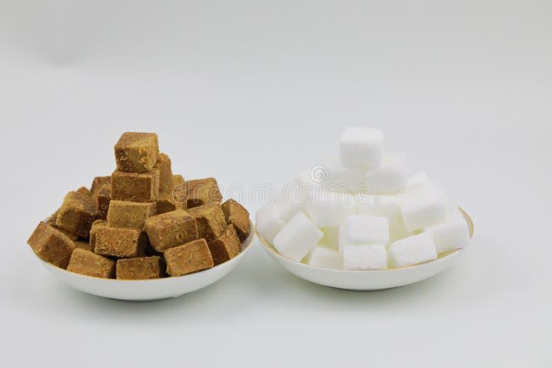 Feche acima da pilha dois de cubos do açúcar mascavado em uma placa branca no fundo branco fotos de stock royalty free