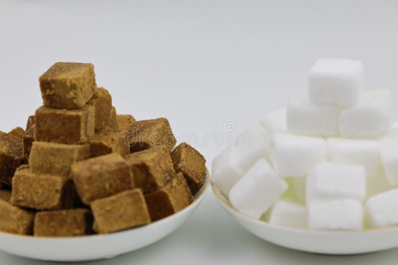 Feche acima da pilha dois de cubos do açúcar mascavado em uma placa branca no fundo branco foto de stock