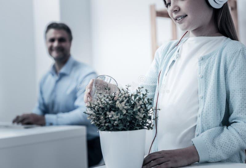 Feche acima da planta molhando da criança esperta imagem de stock