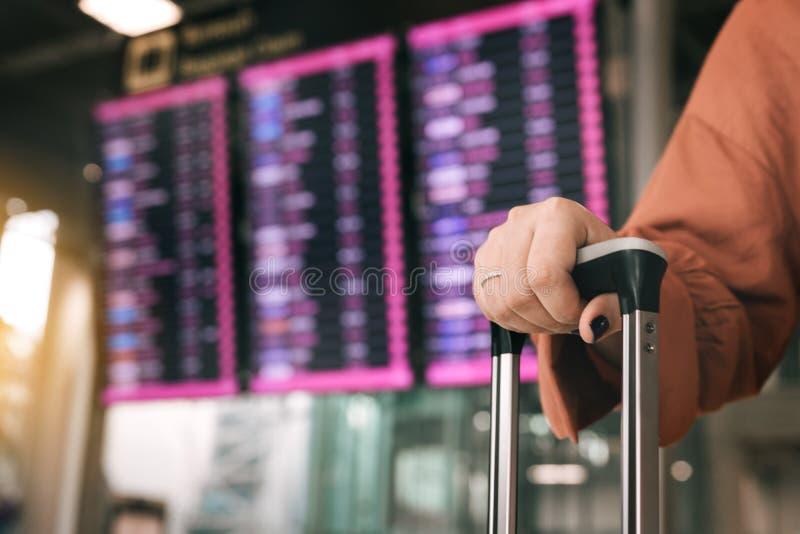 Feche acima da posição da mala de viagem da terra arrendada da mão da mulher no aeroporto que verifica a placa da partida da cheg fotos de stock