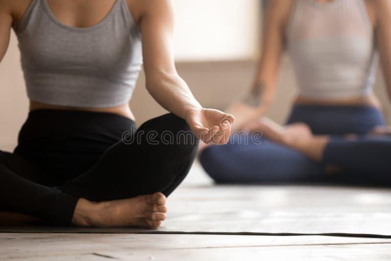 Feche acima da prática fêmea do iogue na posição de lótus imagens de stock royalty free