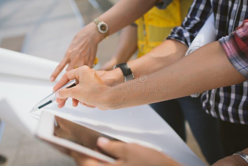 Feche acima da reunião do coordenador da mão para o funcionamento de projeto arquitetónico com as ferramentas do sócio e da engen imagens de stock royalty free