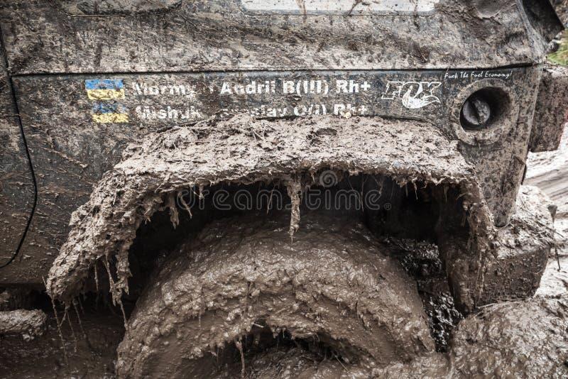 Feche acima da roda do jipe colada em um poço enlameado profundo foto de stock
