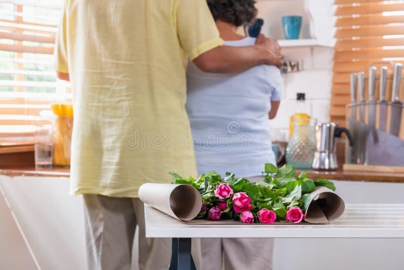 Feche acima da rosa cor-de-rosa com a esposa superior asiática do abraço do marido quando grrangement da flor na tabela na cozinh imagens de stock royalty free