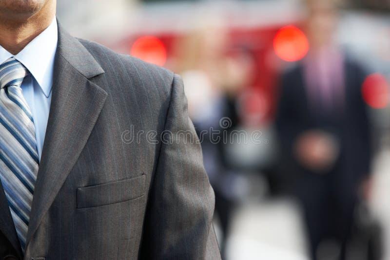 Feche acima da rua de Walking Along City do homem de negócios imagem de stock