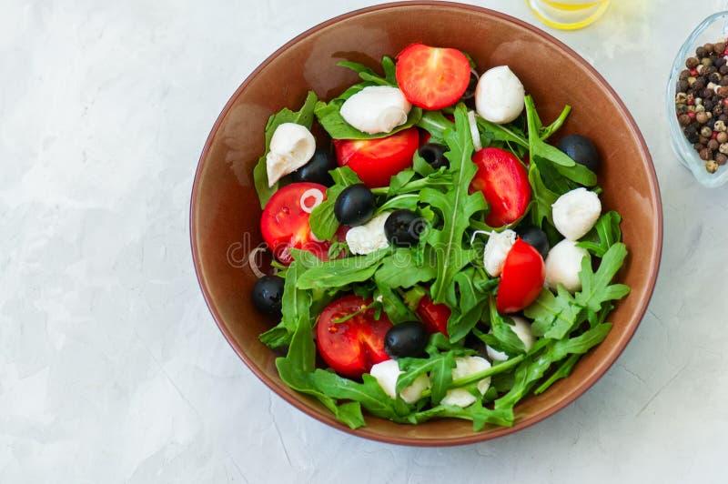 Feche acima da salada fresca com rucola, tomates cereja, azeitonas, sp fotos de stock