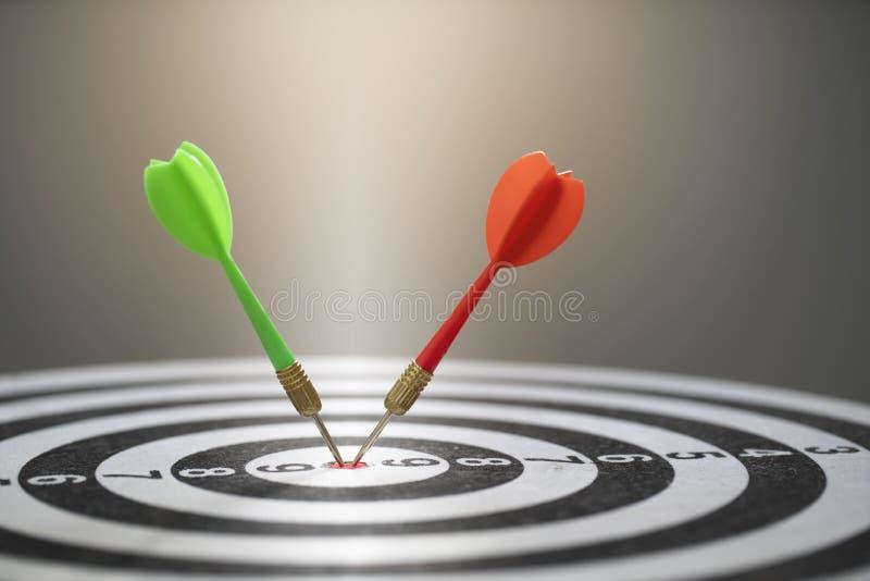 Feche acima da seta vermelha e verde do dardo que bate no centro do alvo do alvo imagens de stock royalty free