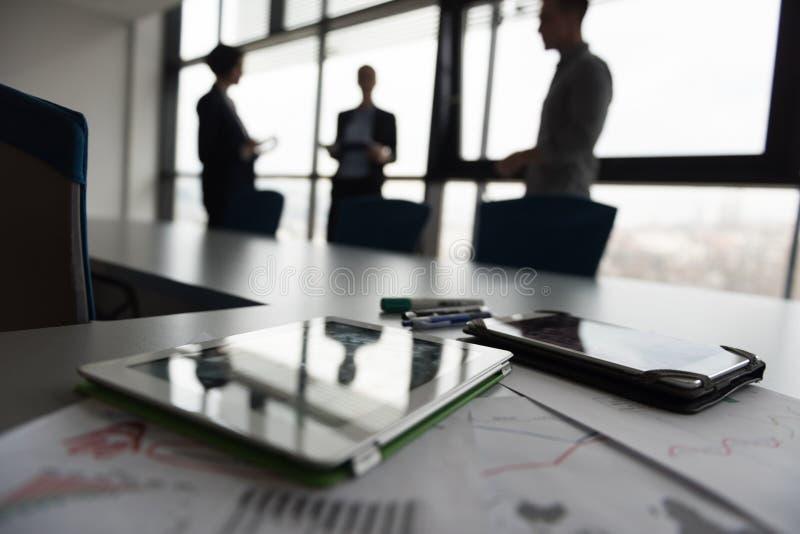 Feche acima da tabuleta, executivos na reunião no fundo imagens de stock royalty free